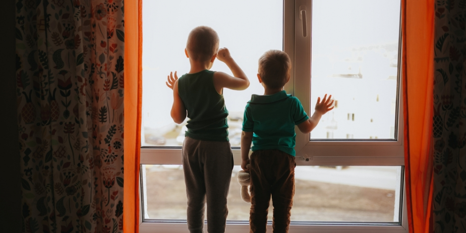 two young children silhouetted inside house standing looking out the window